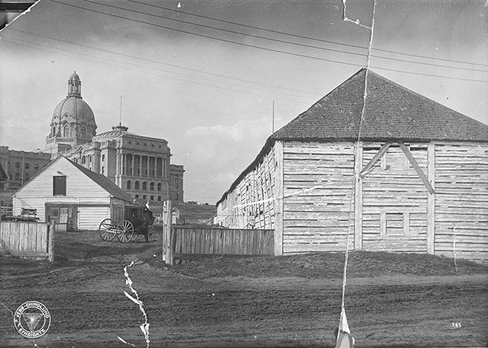 View of the exterior of the Hudson's Bay Company's Fort Edmonton, in front of the new Legislative Building for the Province of Alberta, ca. 1915