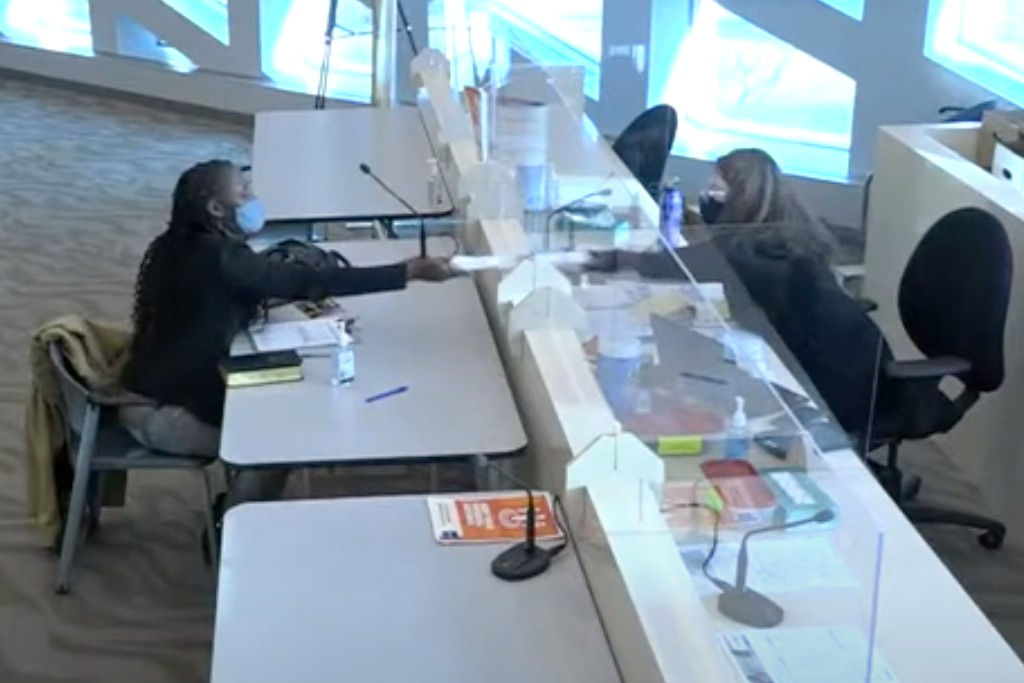 A screenshot from livestreamed video of a candidate and a clerk exchanging papers at City Hall.