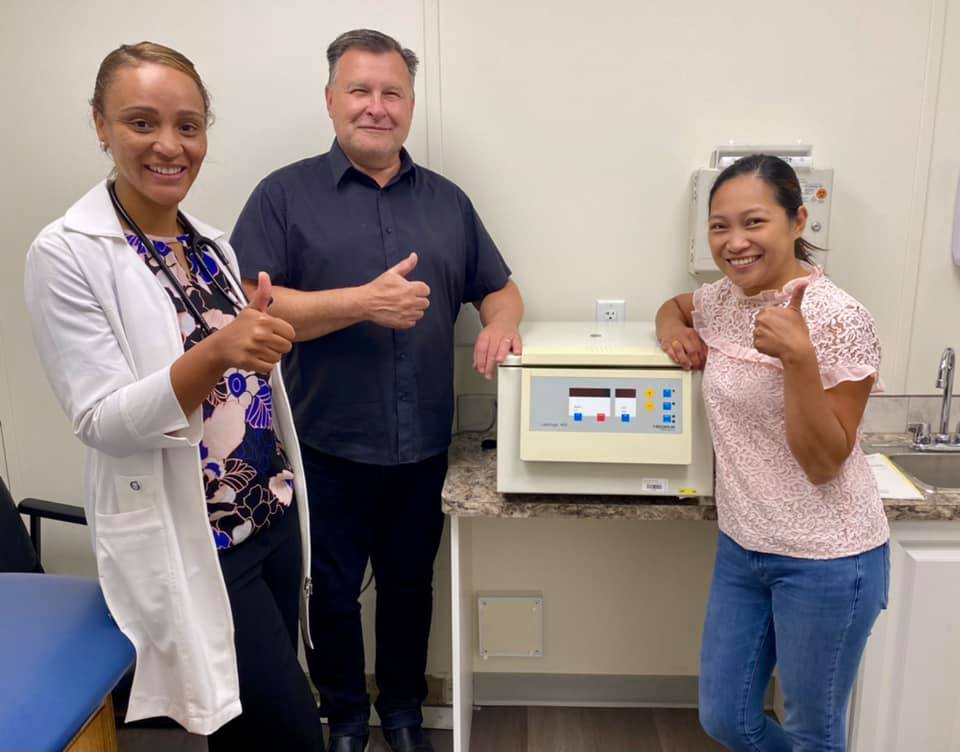 Three people in a medical clinic give a thumbs-up sign beside a centrifuge