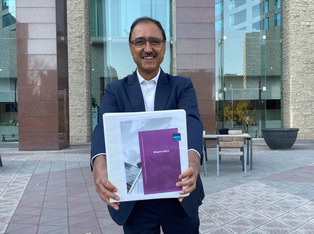 """A smiling Amarjeet Sohi holds a white binder with the words """"Mayor-Elect"""" on the front at City Hall"""